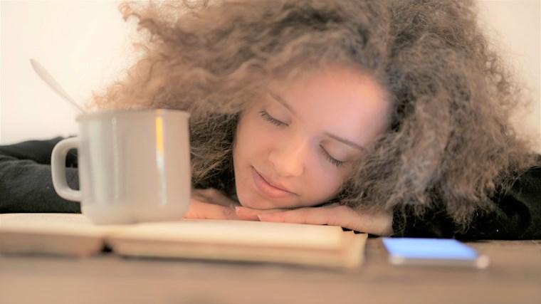 目を閉じてオーディオブックを楽しむ女性